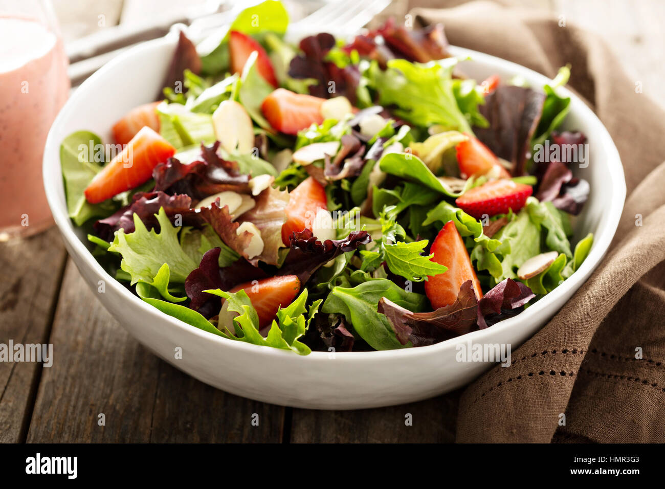 Healthy and colorful salad with spring mix greens and strawberries - Stock Image