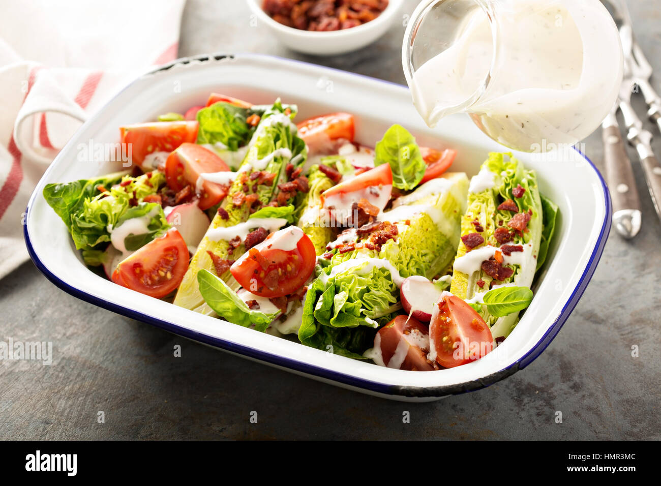 Wedge salad with baby lettuce, cherry tomatoes, bacon and ranch dressing poring over - Stock Image