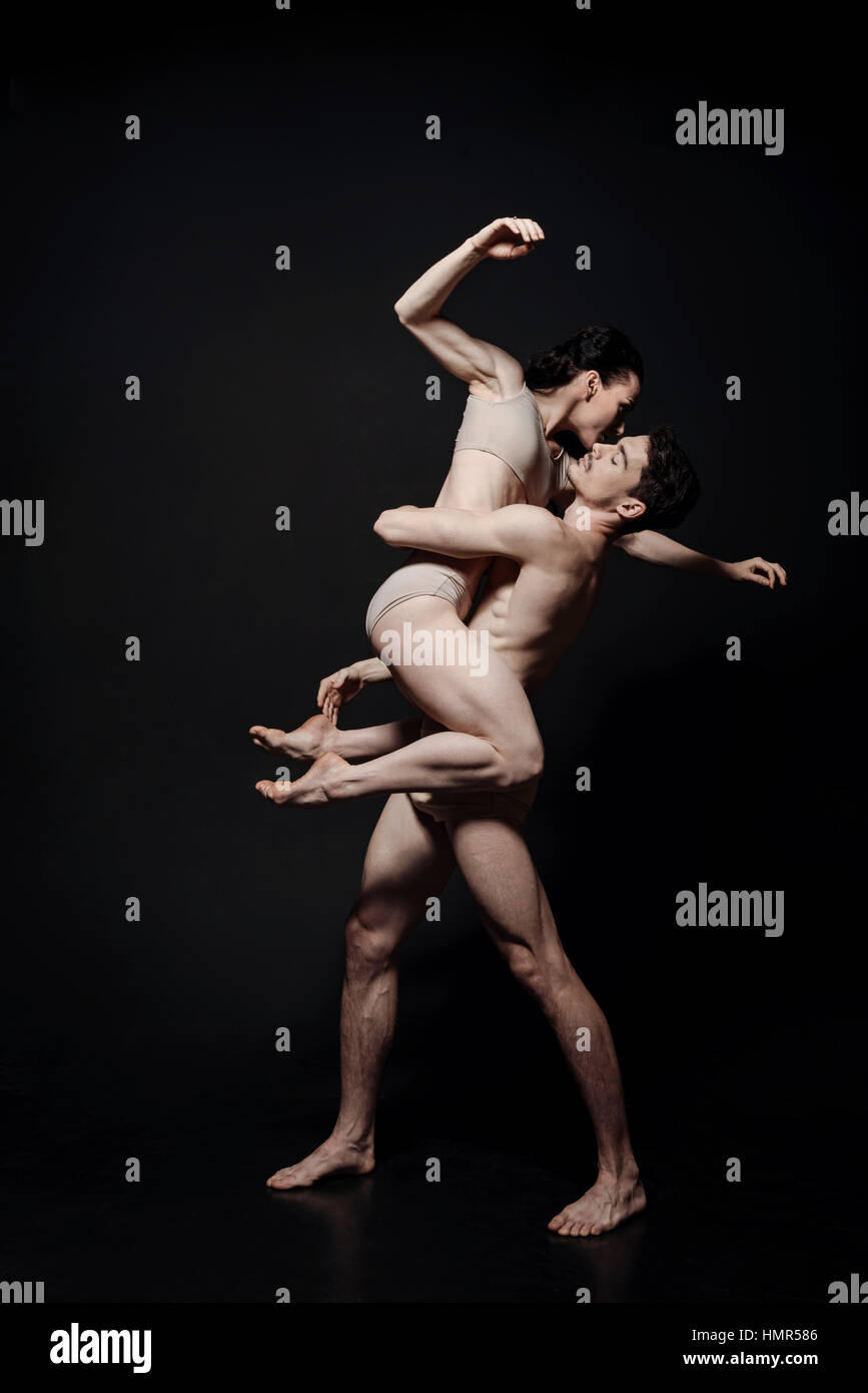 Charismatic young performers dancing in the black colored studio - Stock Image