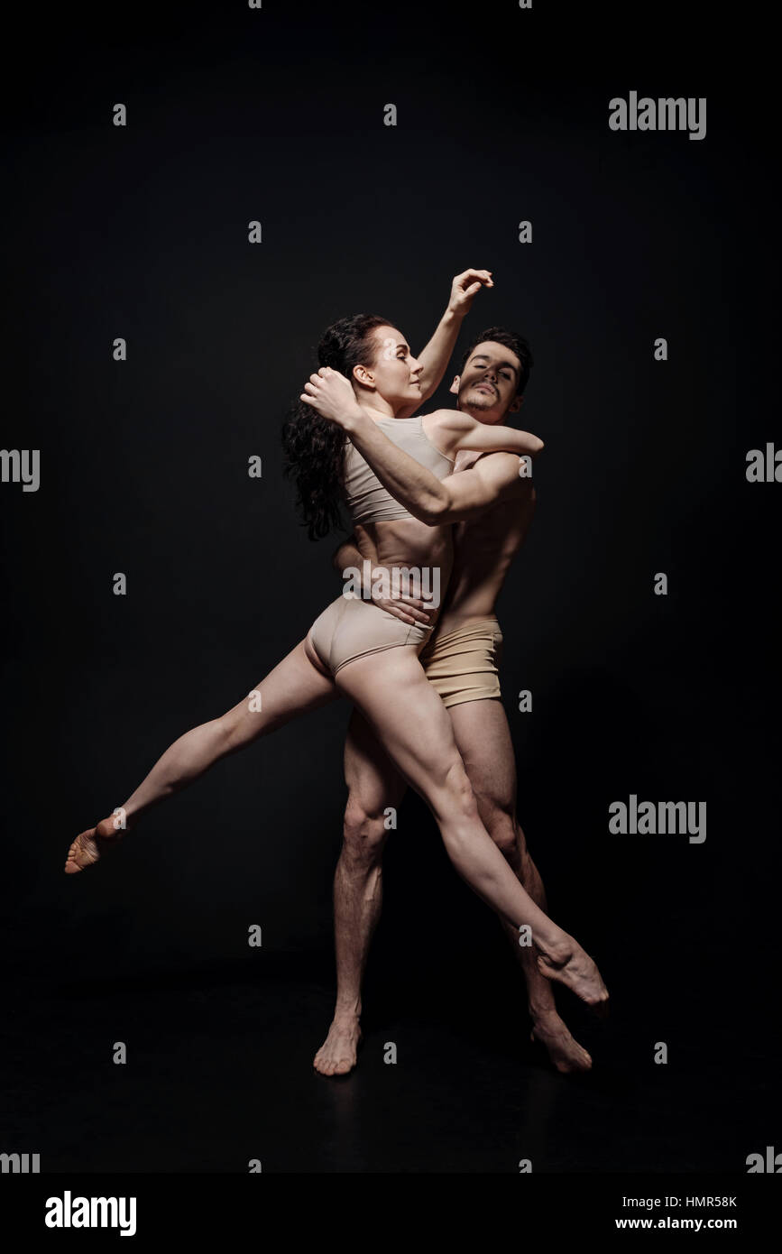 Talented performers dancing isolated in black background - Stock Image