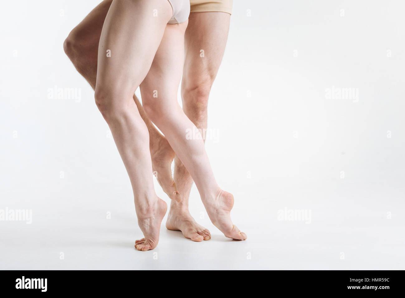 Muscular ballet dancers legs in the white studio - Stock Image