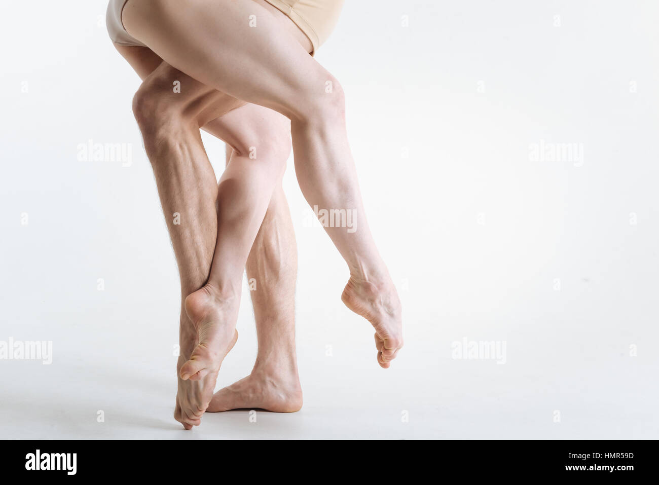 Strong gymnastics legs located in the white colored studio - Stock Image