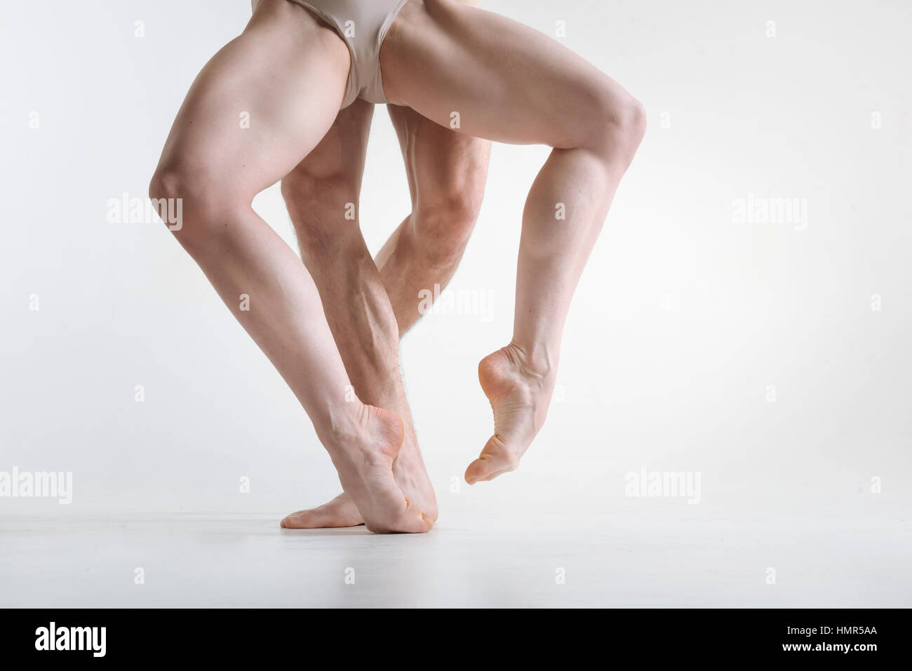 Sportive athletes legs located in the white colored room - Stock Image