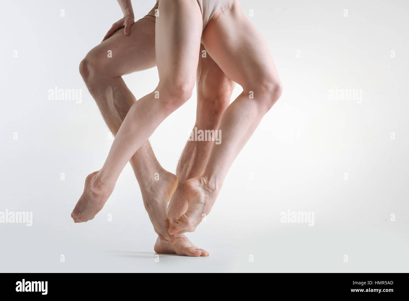 Muscular athletes legs dancing in the white colored studio - Stock Image