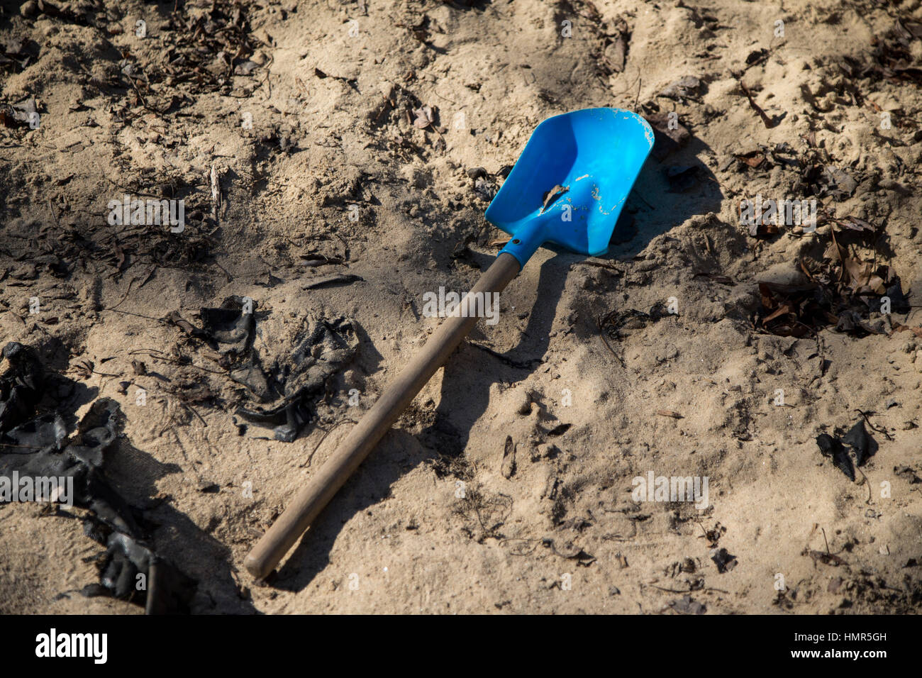 A child's shovel in a sandbox - Stock Image