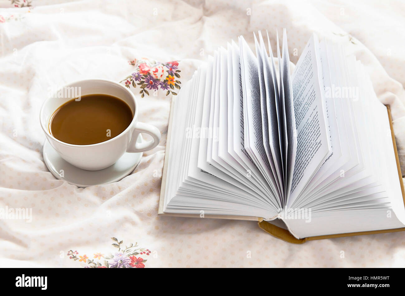 Still-life coffee cup and a book in bed on floral bed sheets - Stock Image