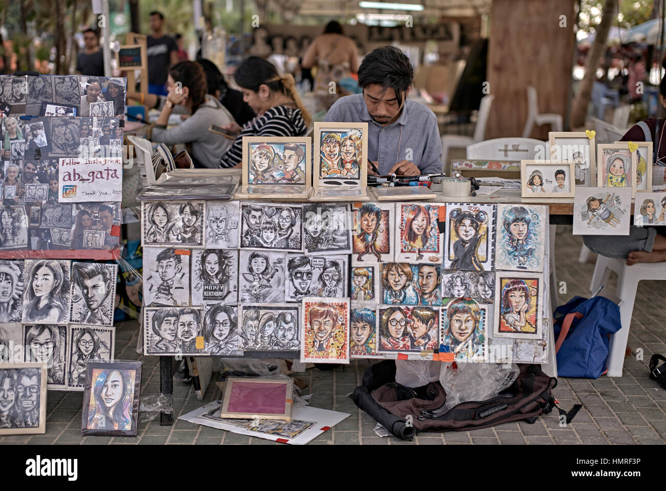 Asian portrait artist drawing caricatures of his subjects. Pattaya Arts Festival 2017. Thailand S. E. Asia - Stock Image