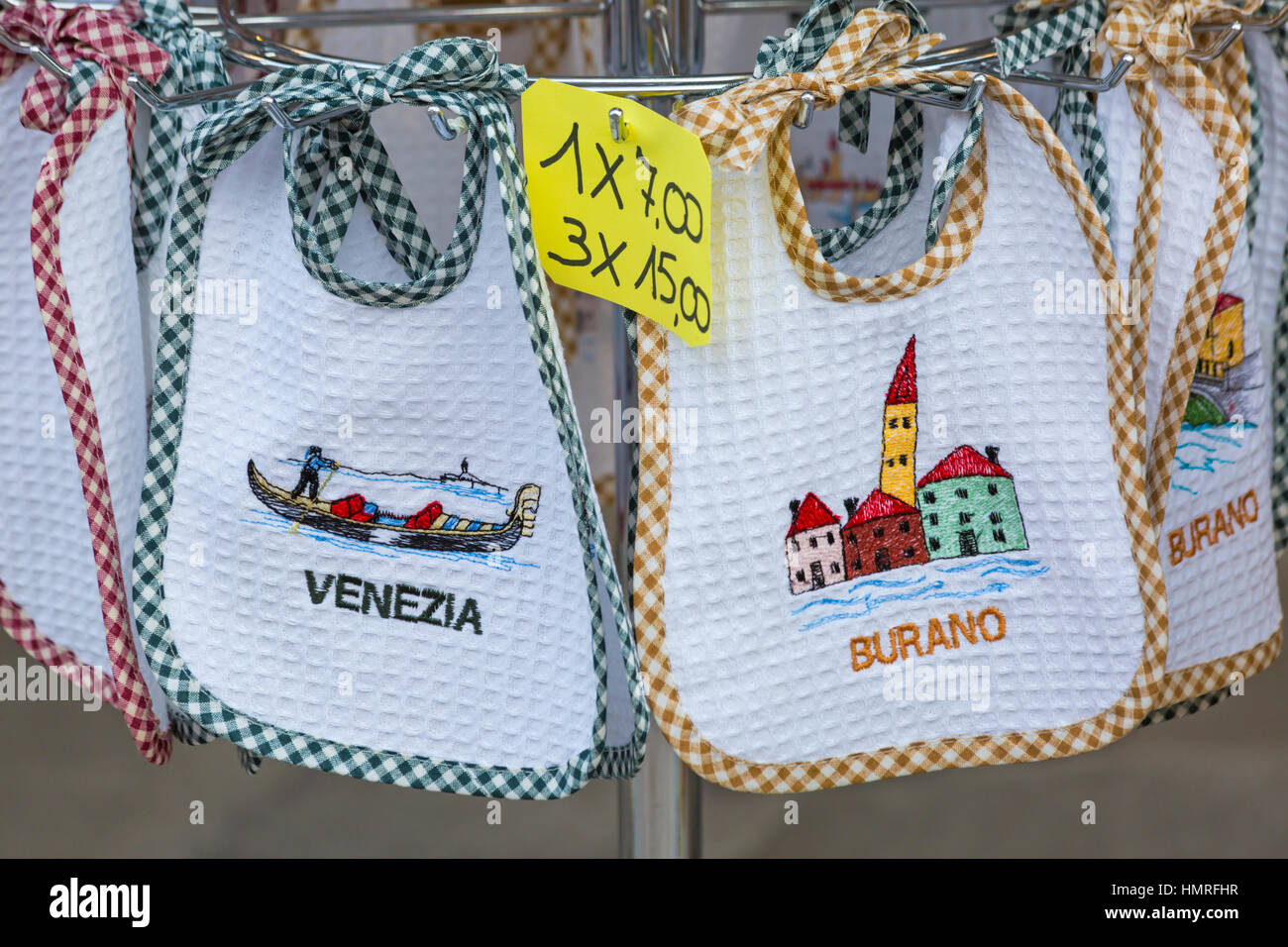 Baby souvenir bibs for sale at Burano, Venice, Italy in January - Stock Image