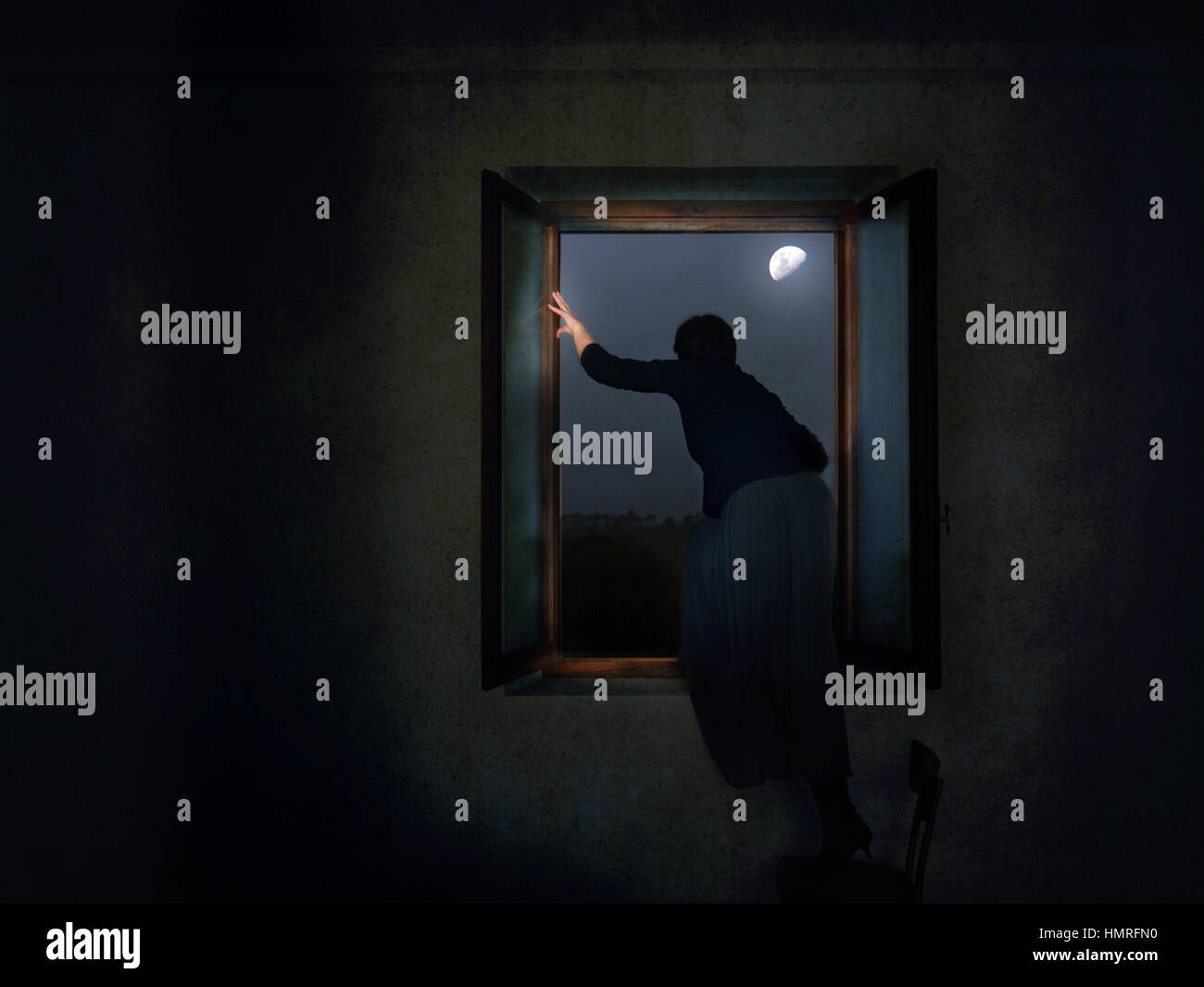 The fugitive, runaway. Woman climbing sneakily out of window. - Stock Image