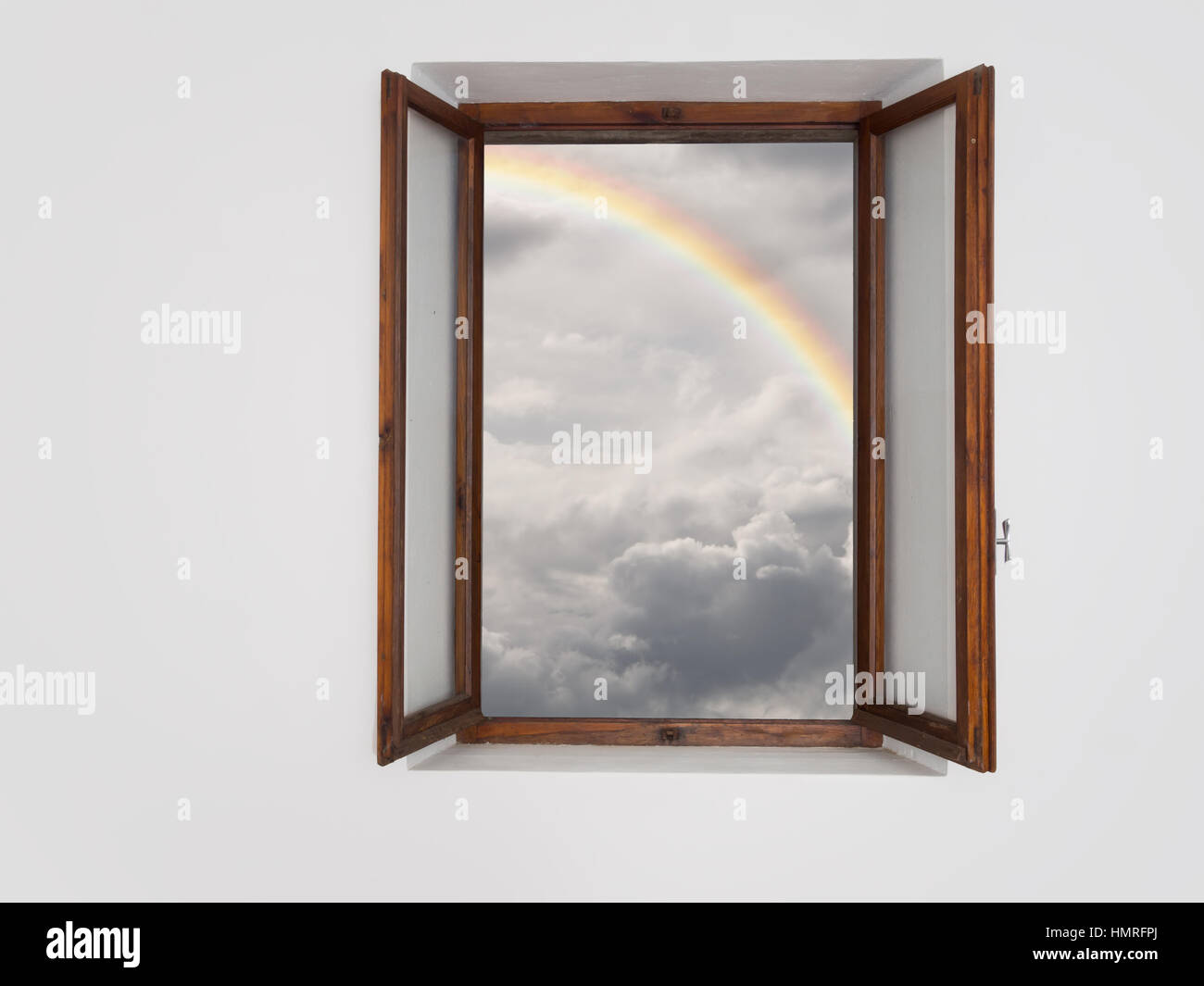 Window onto better times. Clouds but with rainbow. - Stock Image