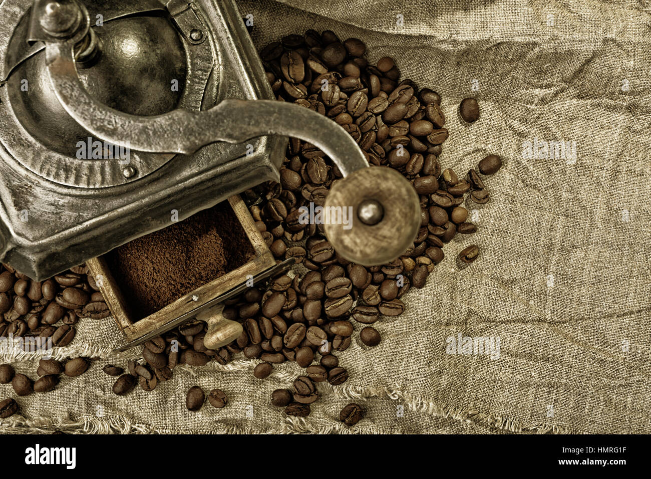 old metal coffee grinder and drawer full of caffee powder on old burlap in sepia tones - Stock Image
