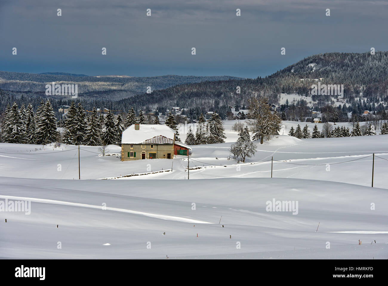 Remote farm house in thE snow-covered landscape of the Swiss Jura mountain range near the hamlet La Cure, Vaud, - Stock Image