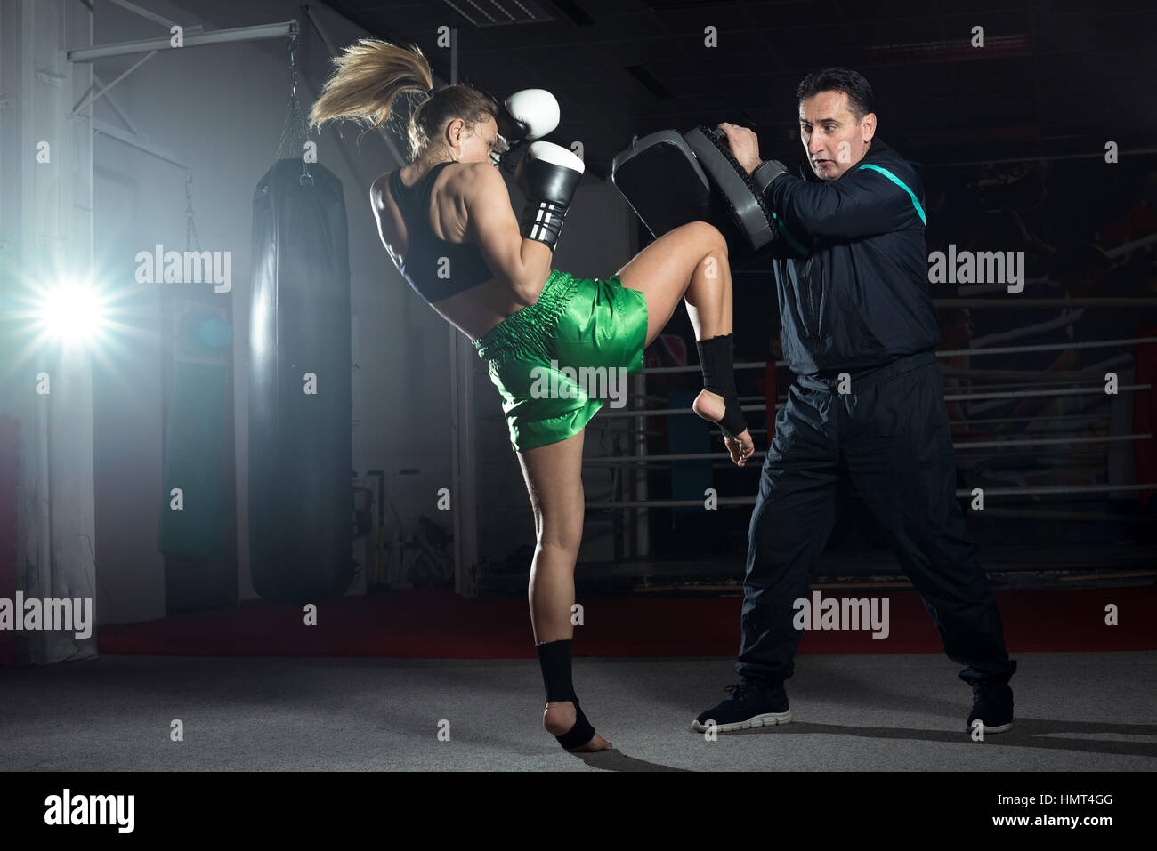 Girl doing knee kick exercise during kickboxing training with personal trainer - Stock Image