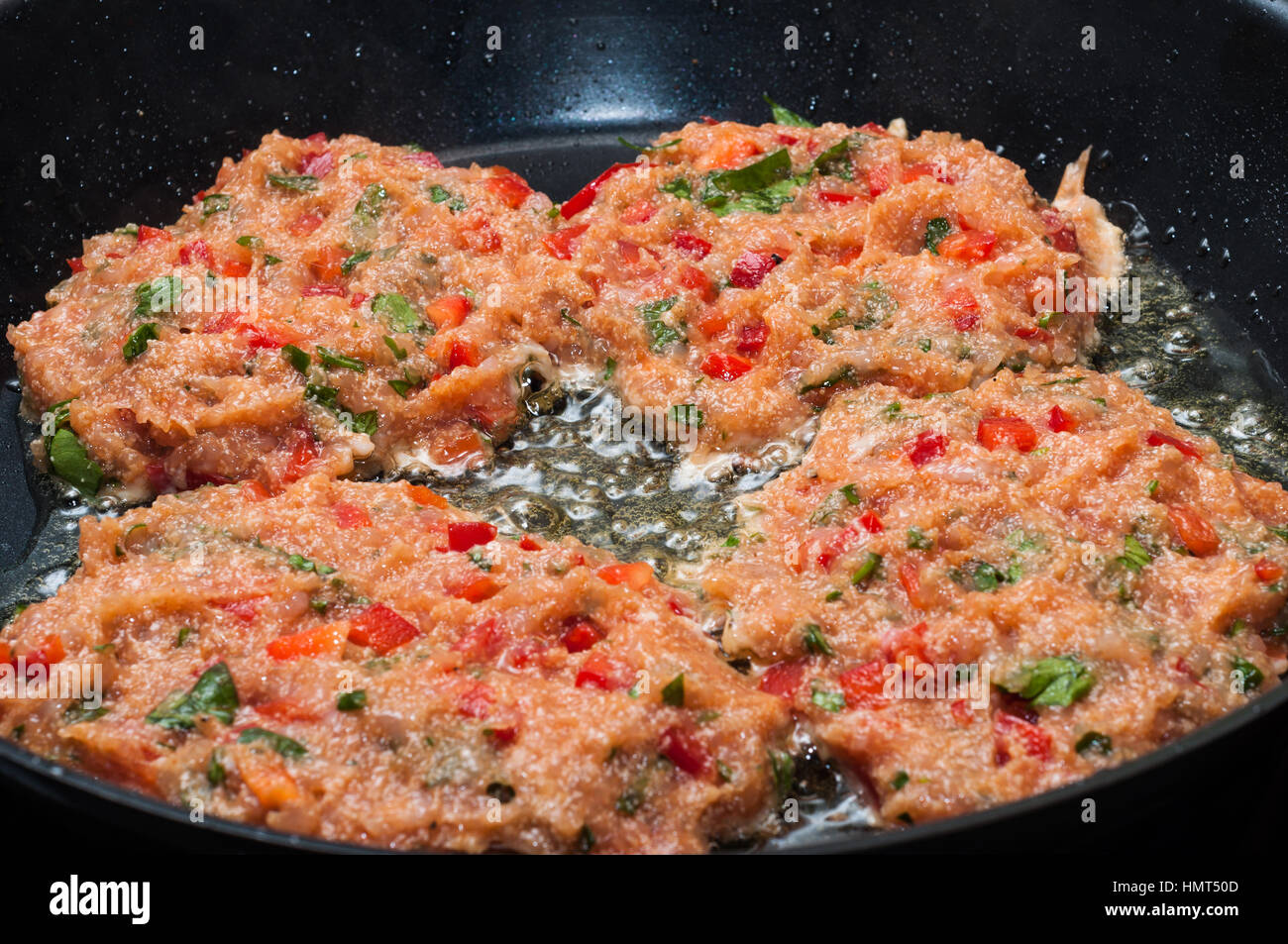 cooking home made meatballs with vegetables in pan on ceramic stove - Stock Image