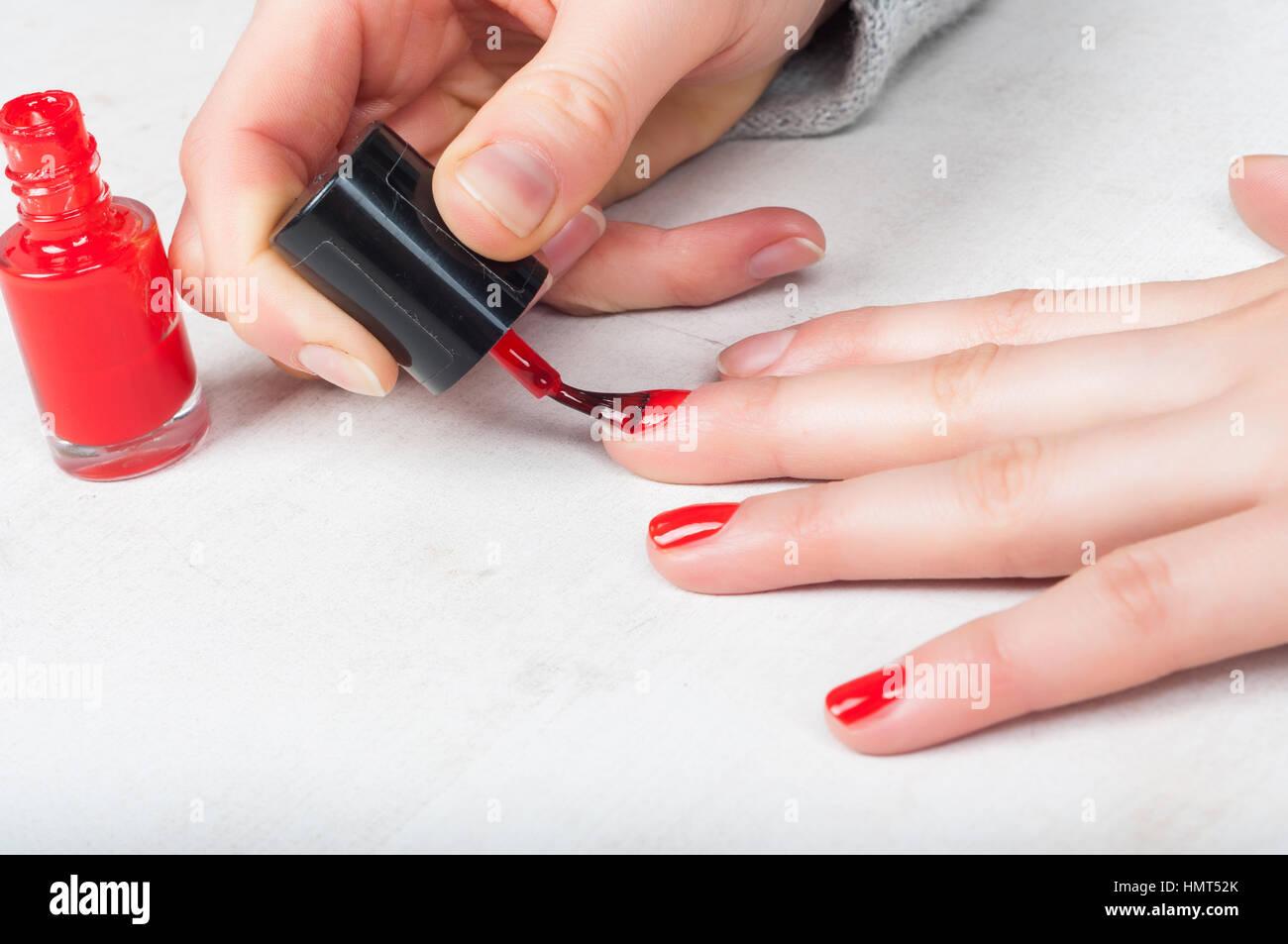 Using applicator brush to apply red polish to fingernail, self made ...