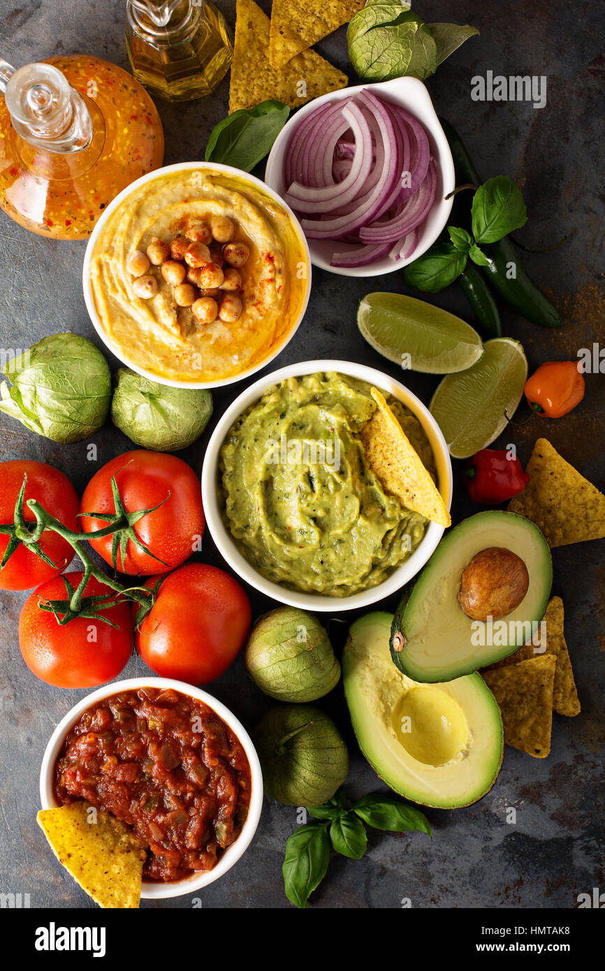 Homemade hummus, salsa and guacamole with corn chips and vegetables overhead view - Stock Image