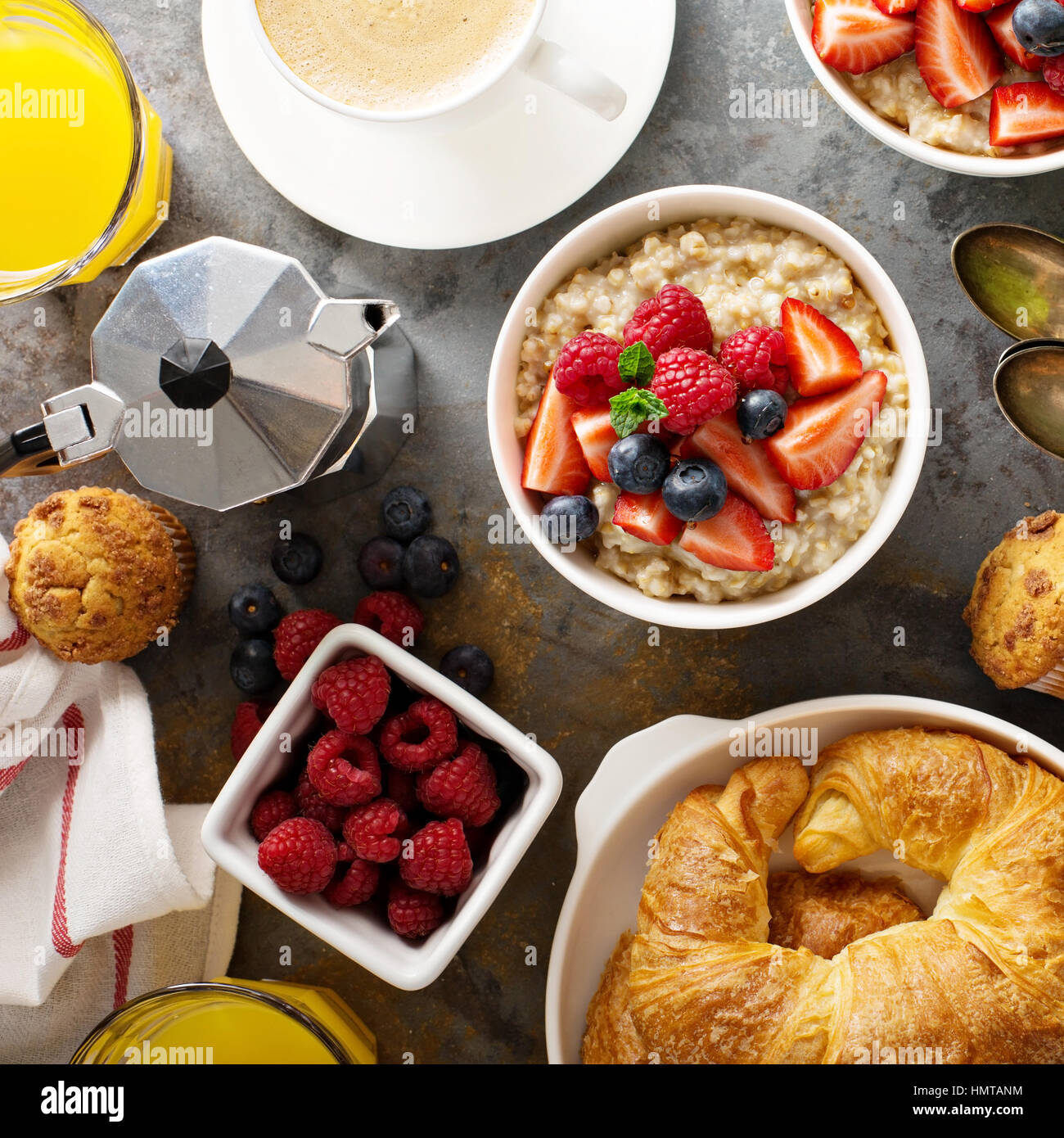 Breakfast table with oatmeal porridge, croissants, fresh fruit and muffins overhead shot - Stock Image
