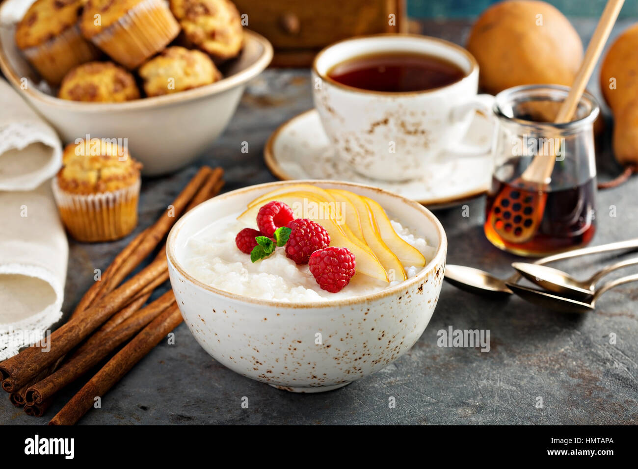 Rice pudding with raspberries and sliced pears for breakfast - Stock Image