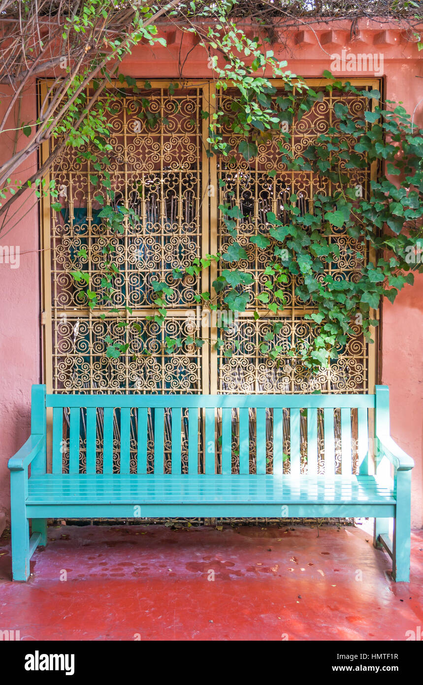 Blue bench in leafy alcove. - Stock Image