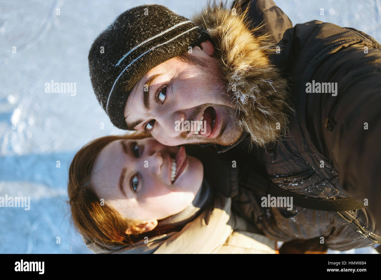 Winter portrait of beautiful traveling couple,hiker laughing couple, emotional man and tongue girl,crazy selfie,hikers. - Stock Image