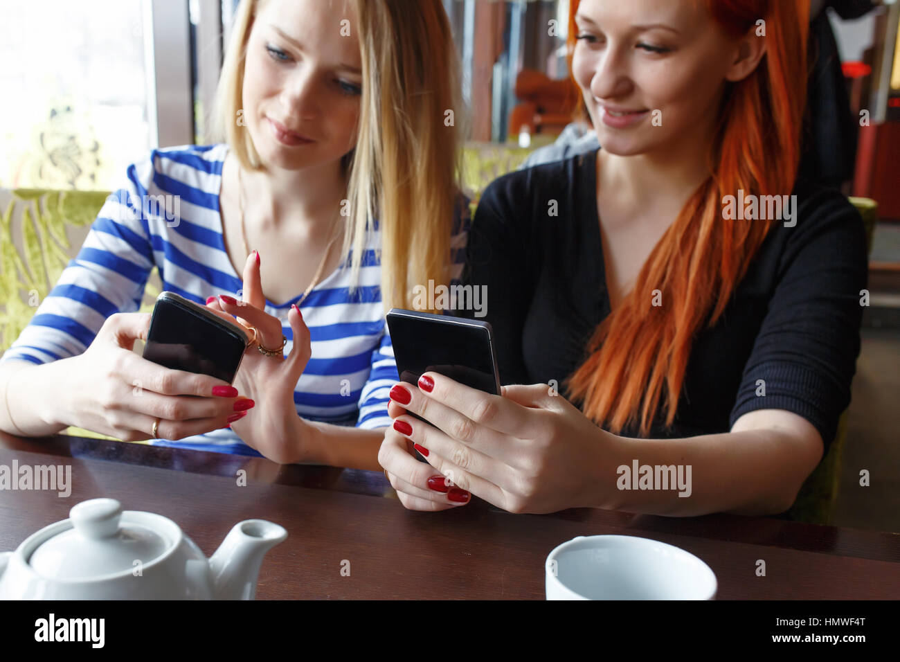 Two women having fun at the cafe and looking at smart phone. - Stock Image