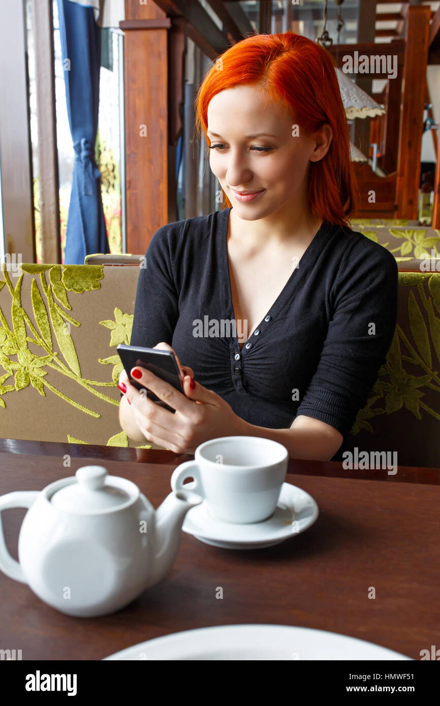 Portrait of beautiful girl in hat using her mobile phone in cafe. Tonned. Selective focus. Stock Photo