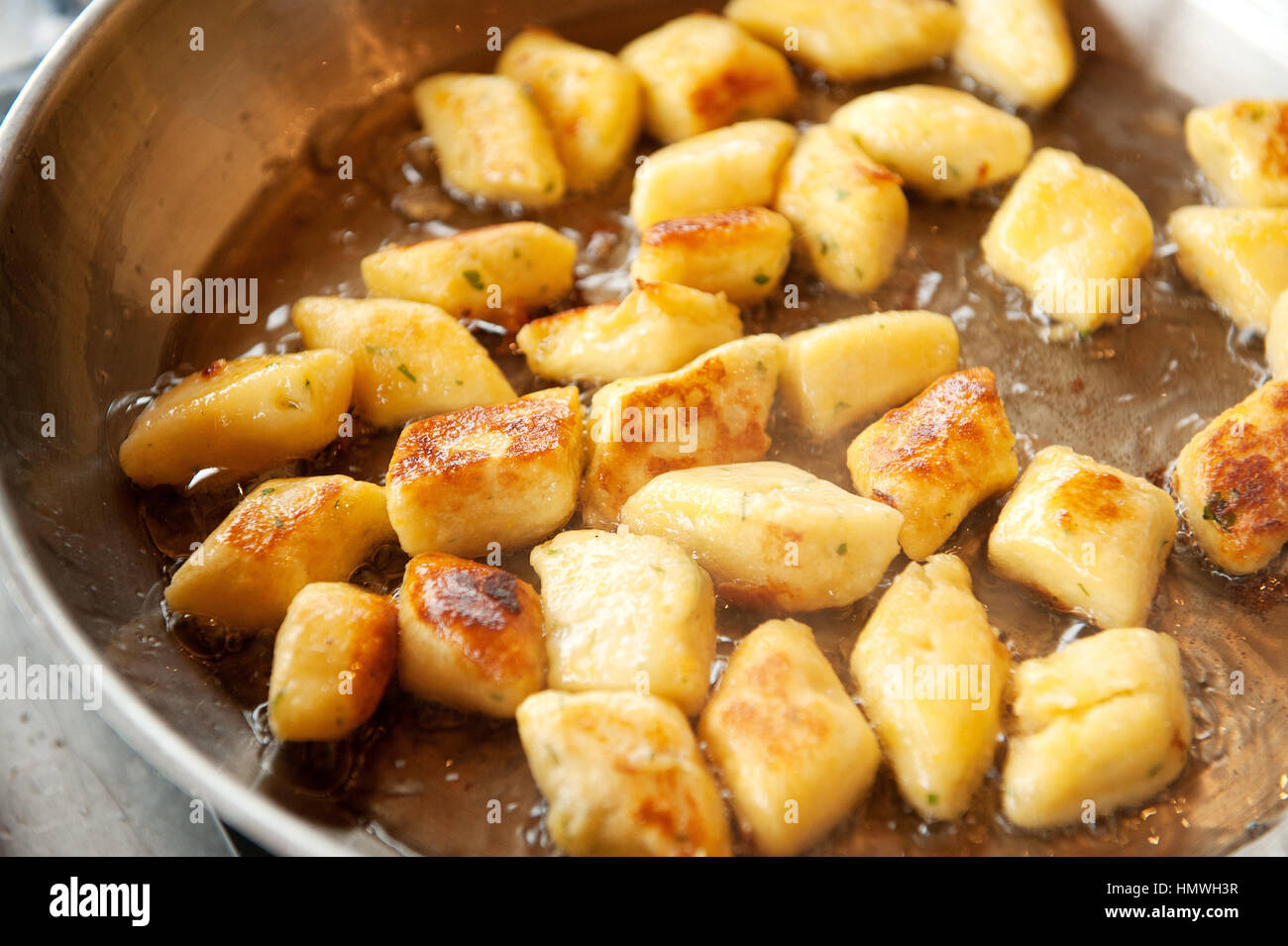 Gnocchi dumplings fry in duck fat in a skillet pan.    Gnocchi are various thick, soft dough dumplings that may - Stock Image
