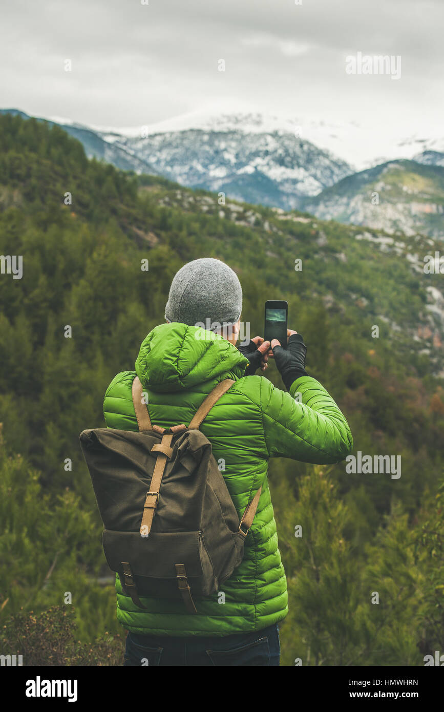 Young man traveller wearing green jacket making photo of slopes and mountains with snowy peaks in Dim Cay district - Stock Image