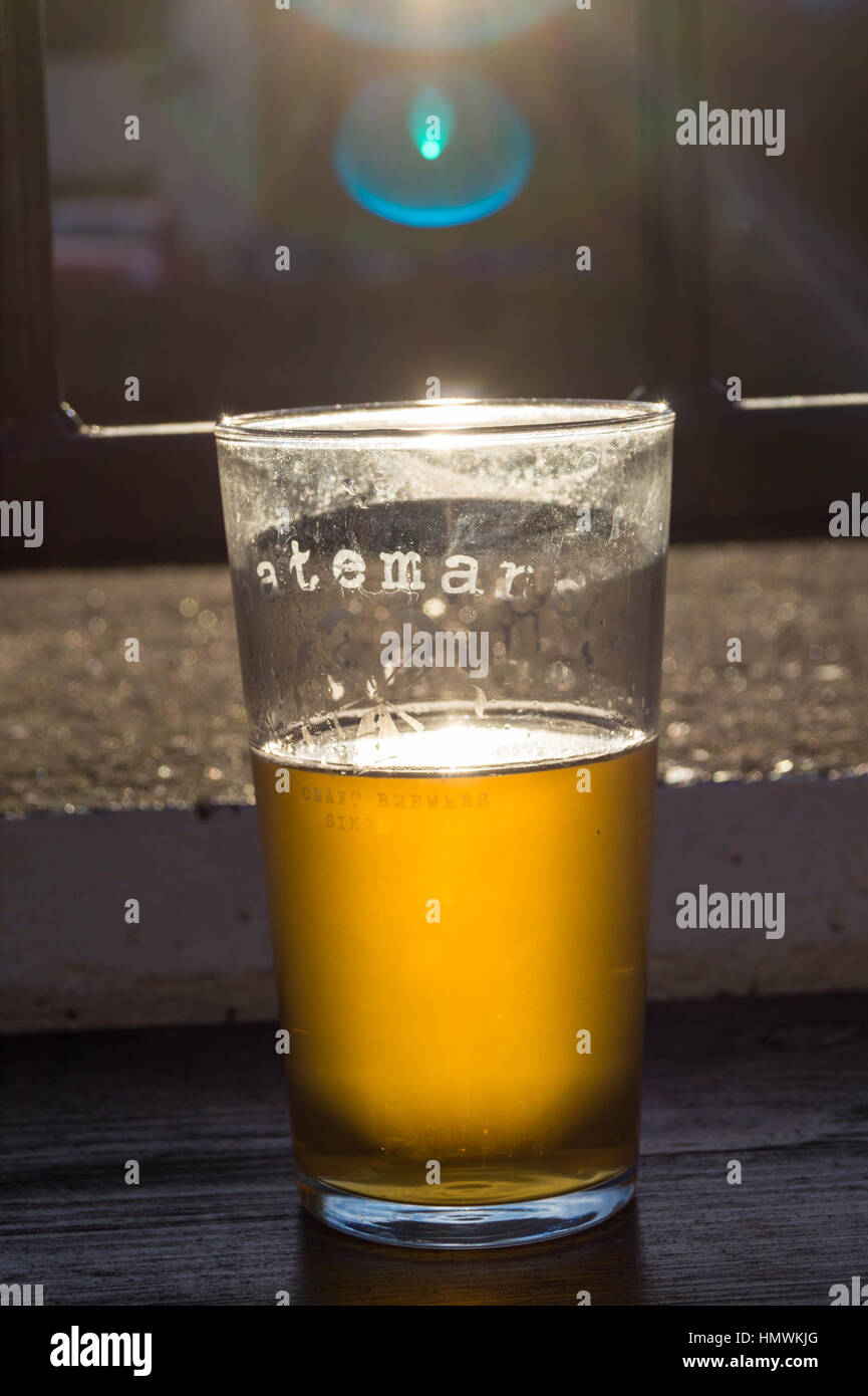 A pint of Batemans Gold beer with sunlight shining through it - Stock Image