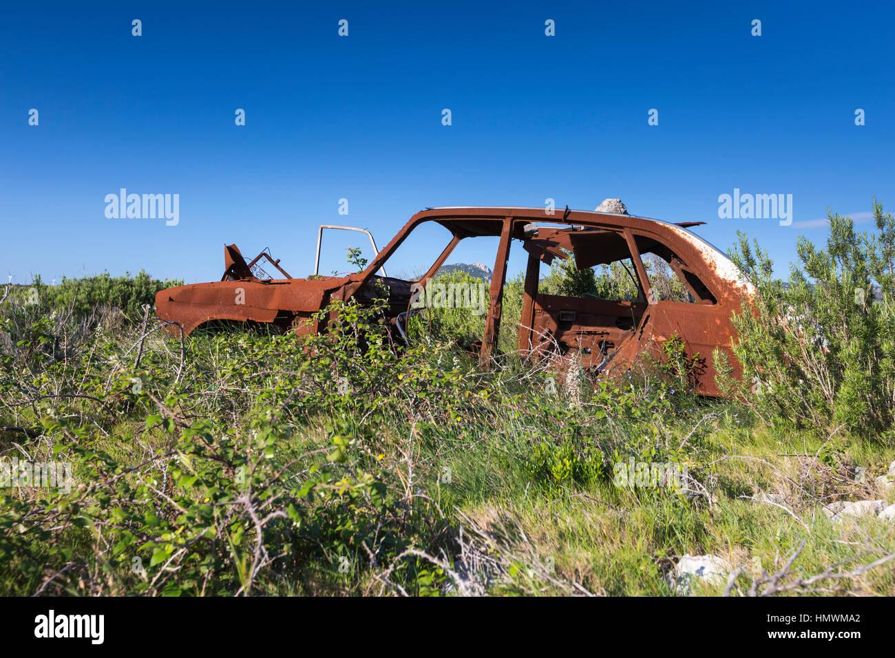 Landscape view of burnt out car amongst heathland vegetation, Feuilla Plateau, Aude, France in June 2016. Stock Photo