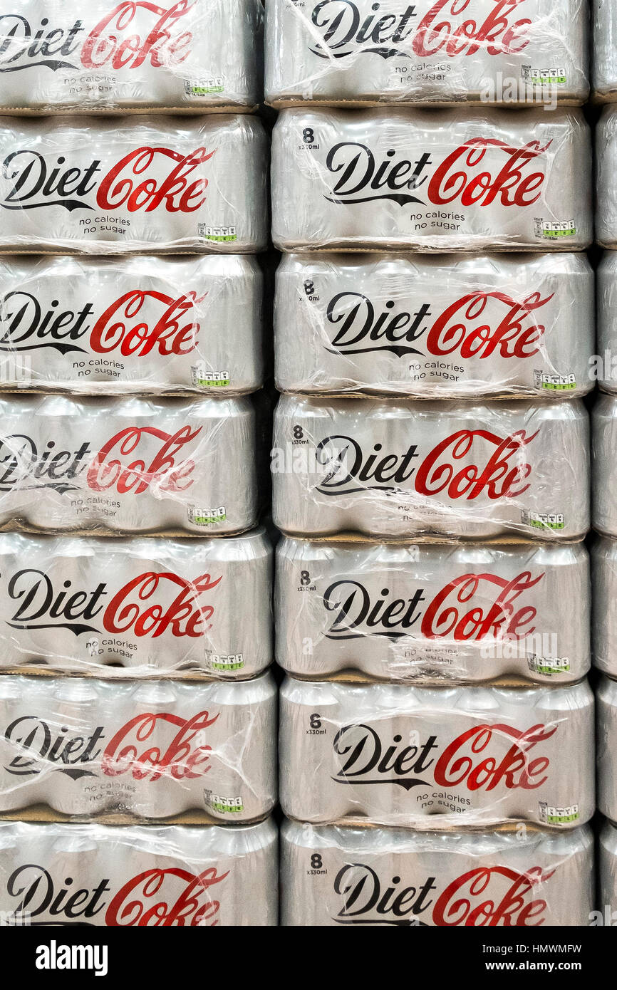 Plastic wrapped packs of Diet Coke stacked up and on sale inside a Morrisons supermarket. - Stock Image