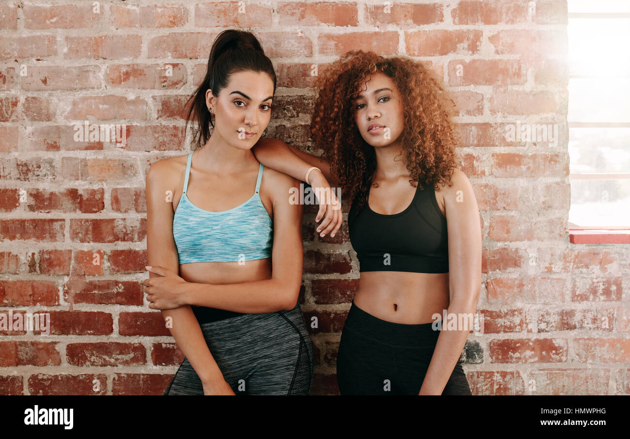 Portrait of sporty young woman standing against wall. Two fitness females in gym after workout. - Stock Image
