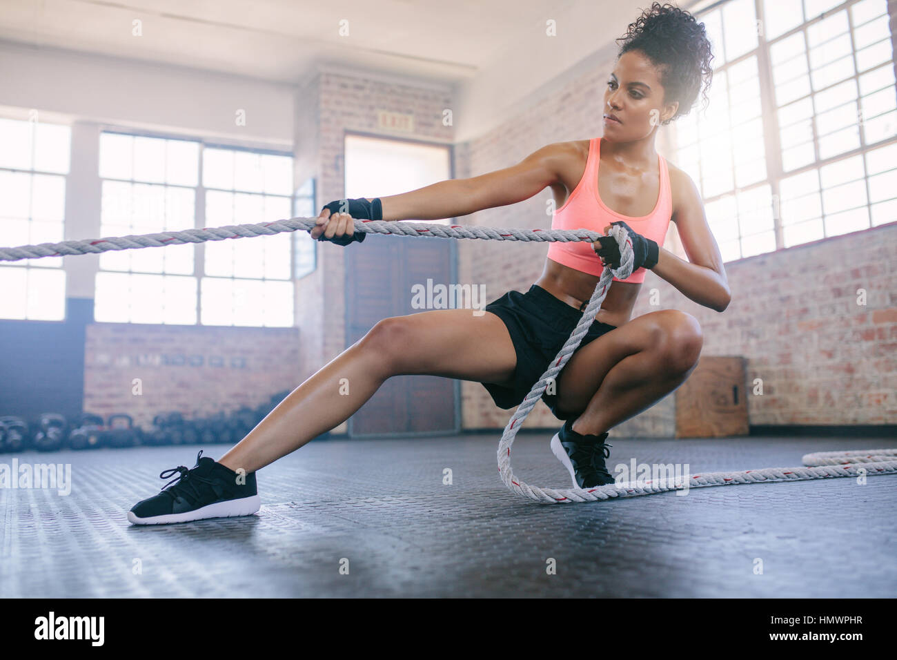 Shot of young african woman doing exercises with rope at a gym. Fitness female pulling rope at gym. - Stock Image