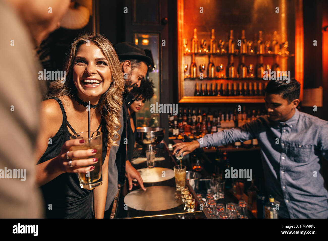 Beautiful young woman with her friends at bar. Young people enjoying a night at club. - Stock Image