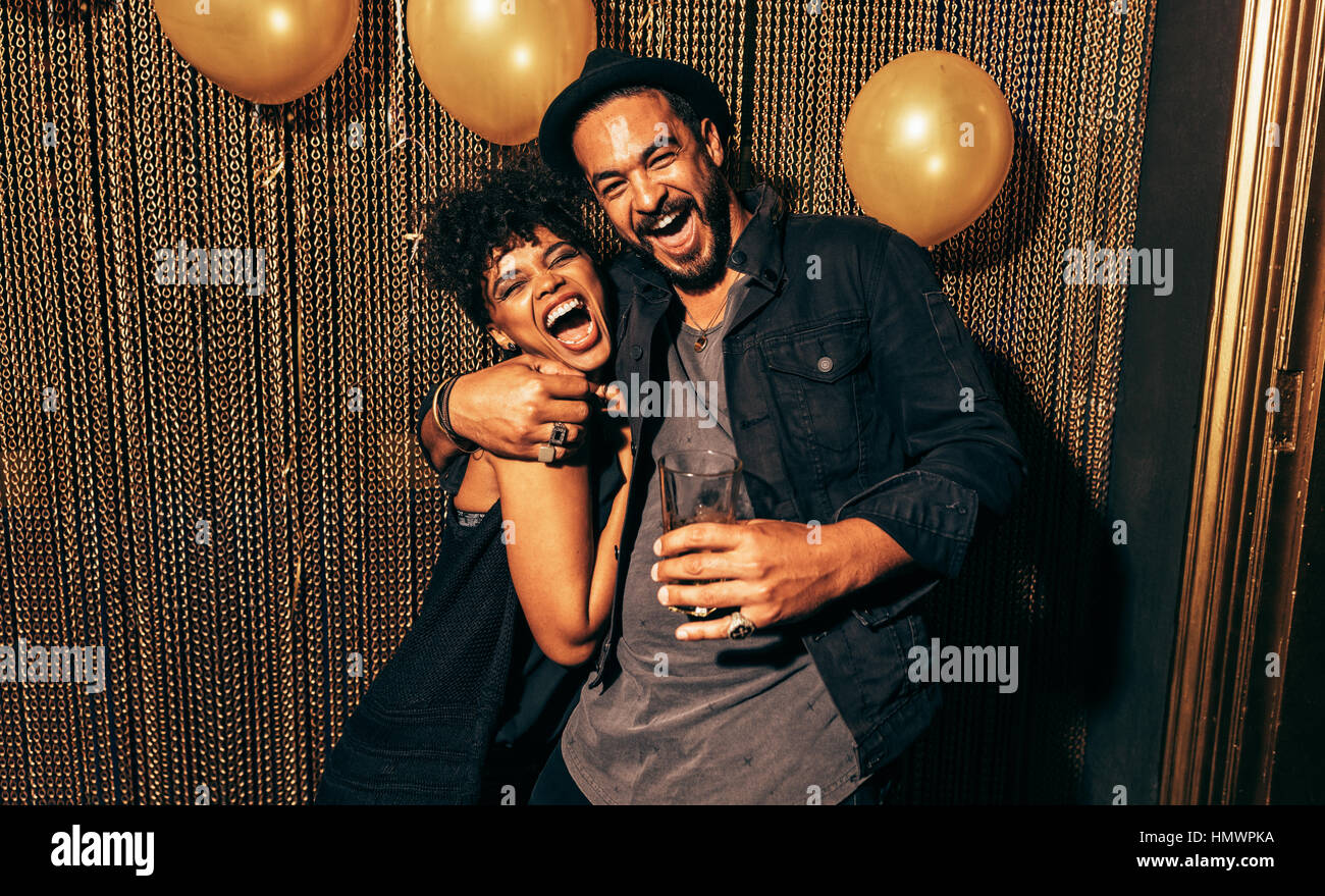 Image of happy young couple having fun at disco. Young man and woman enjoying a party. - Stock Image