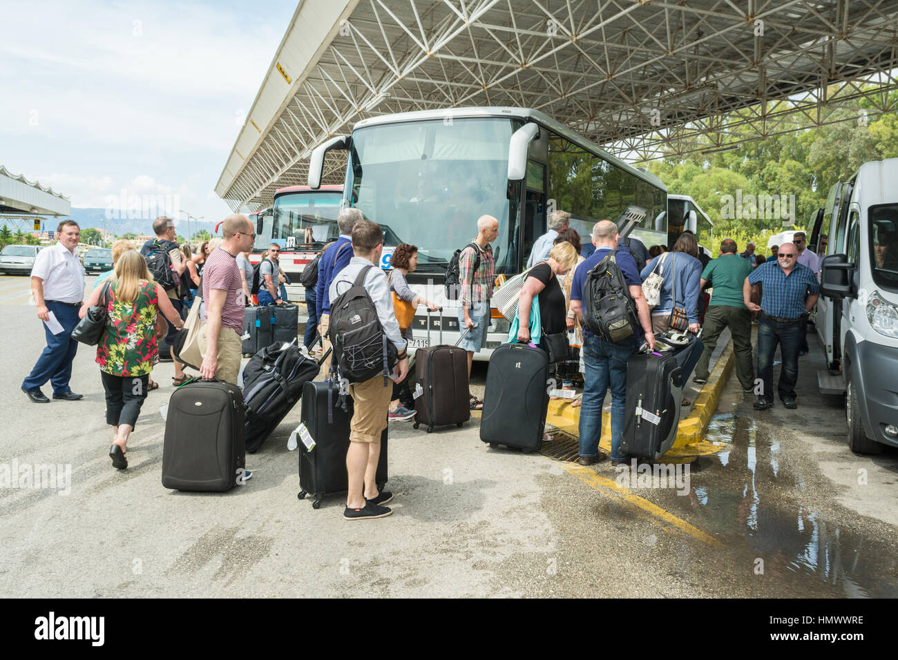 Package holiday airport transfer - tourists with luggage boarding a coach at Corfu airport for transfer to their - Stock Image