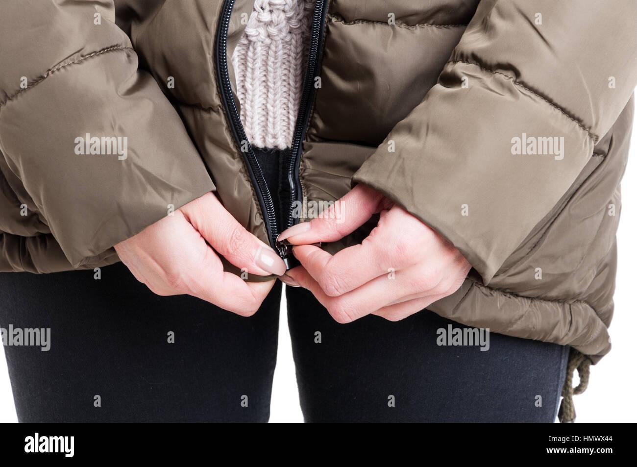 Close-up of lady zipping winter jacket isoalated on white background - Stock Image