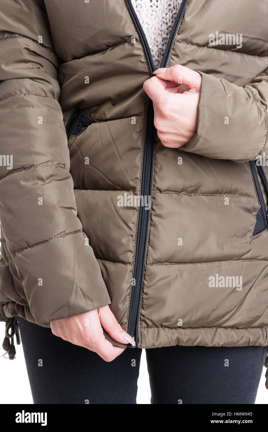 Close-up of lady zipping winter jacket isolated on white background - Stock Image