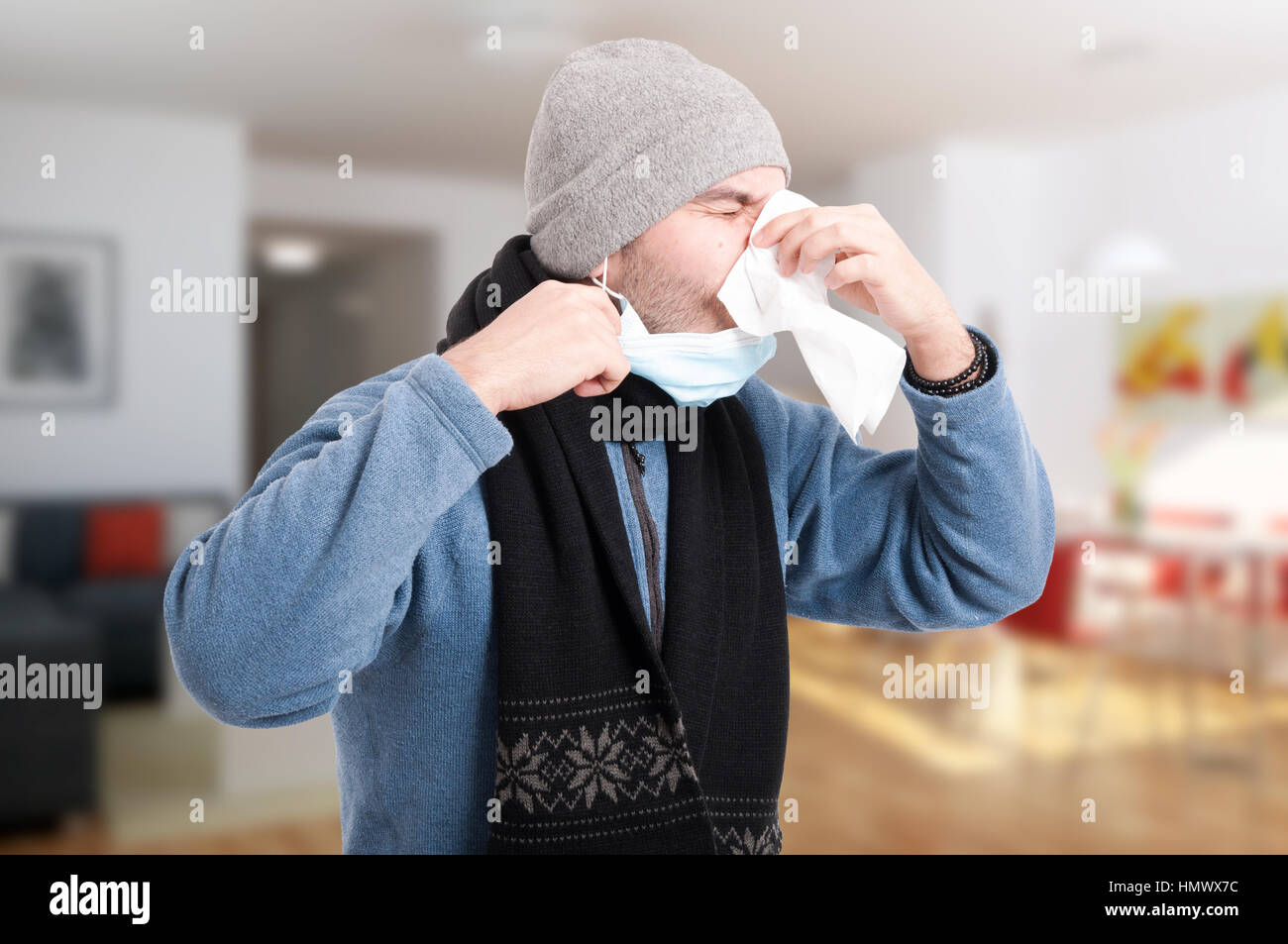 Man with flu and immunity problem blowing his nose into napkin as sickness concept - Stock Image