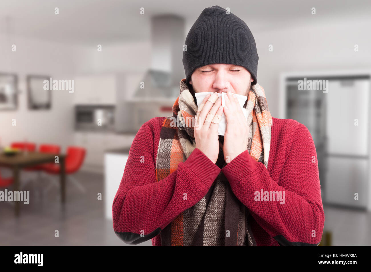 Portrait of ill man with sore throat sneezing in a napkin inside the house - Stock Image