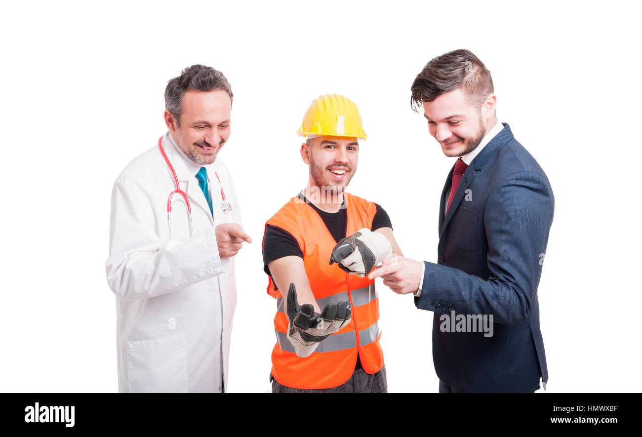 Cheerful group of businessman, doctor and engineer holding something and all pointing at his hand isolated on white Stock Photo