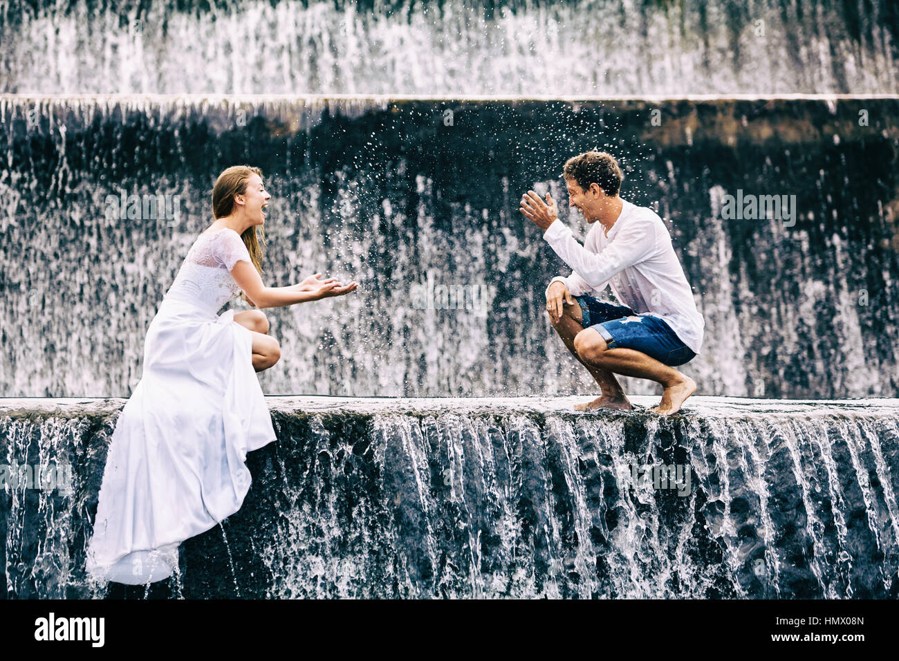 Happy family on honeymoon holidays - married loving couple splashing with fun under falling water in cascade waterfall - Stock Image