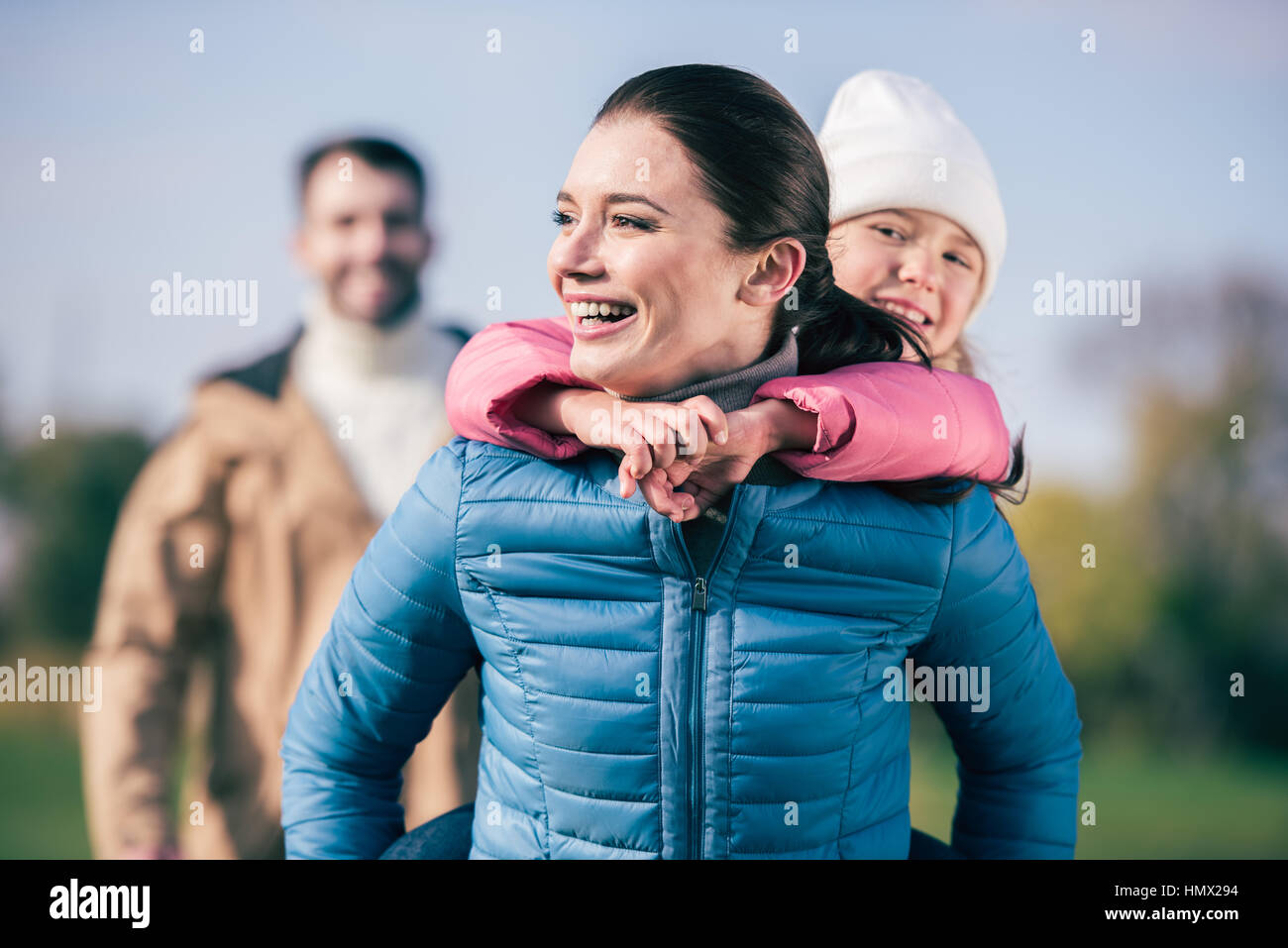 Cheerful mother piggybacking little daughter Stock Photo