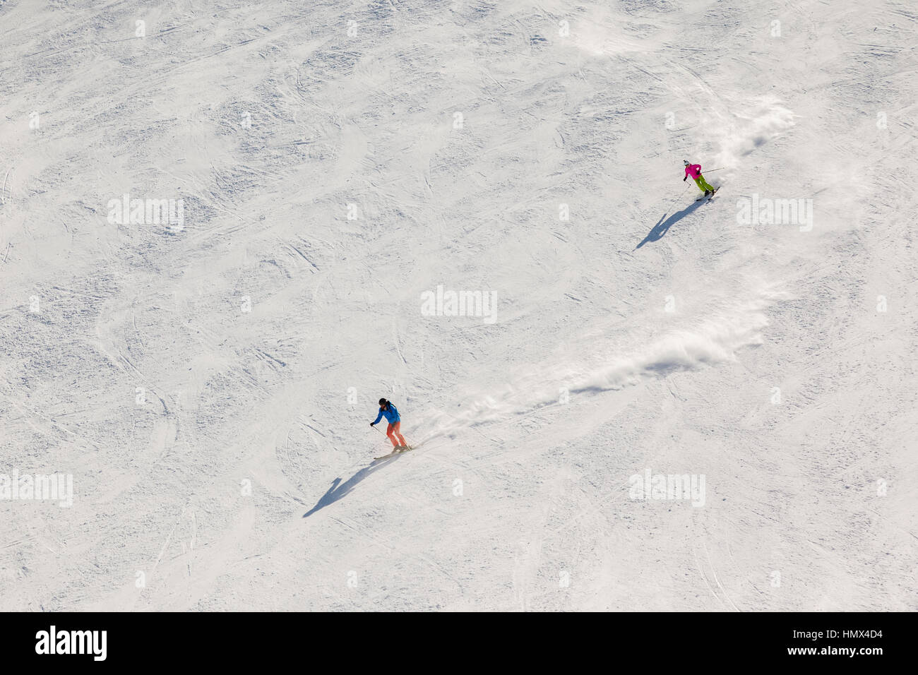 Two skiers on a steep black ski run with trails of snow dust behind them. - Stock Image