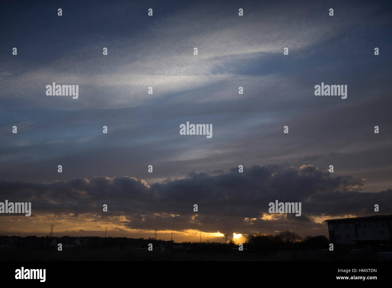 Dartford, Kent, UK. 7th February 2017. A stormy sunset near Dartford Kent. The sun is setting over a new housing Stock Photo