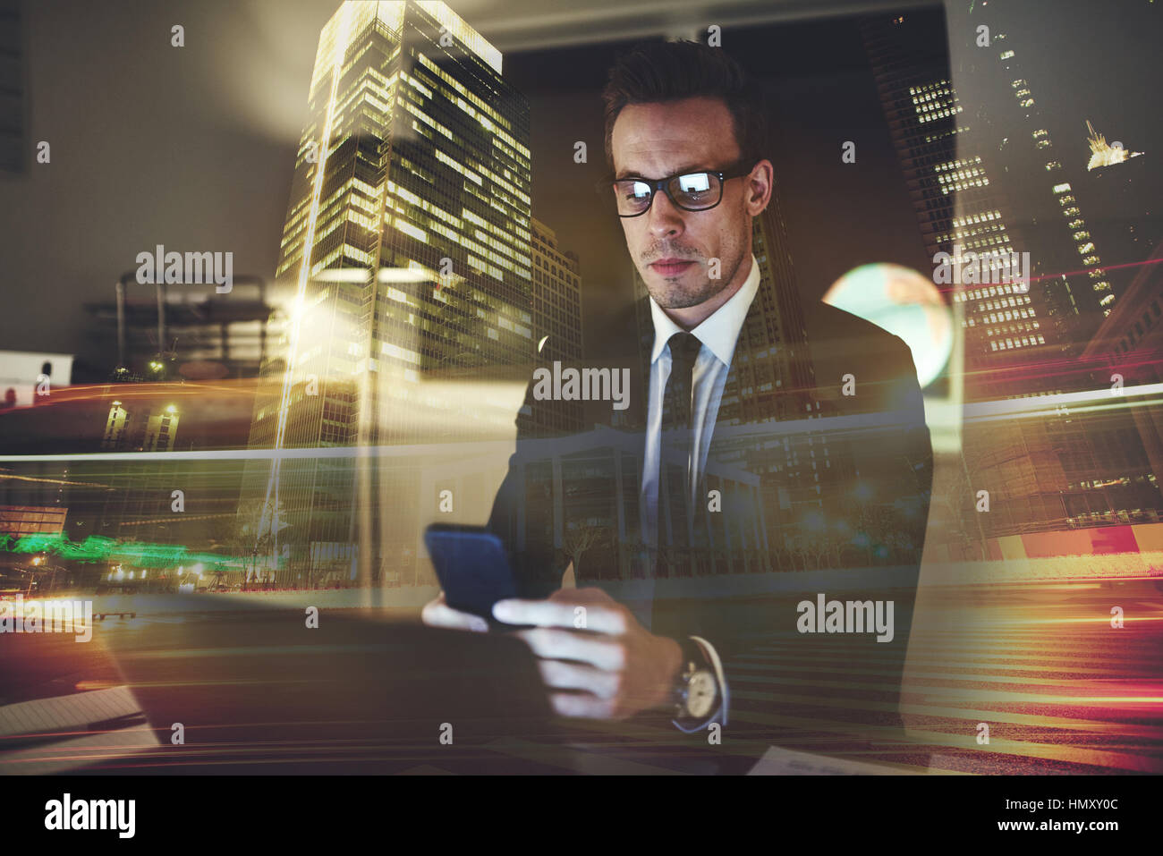 Serious concentrated businessman looking at phone, sitting at office at night, Big City Office Concept - Stock Image