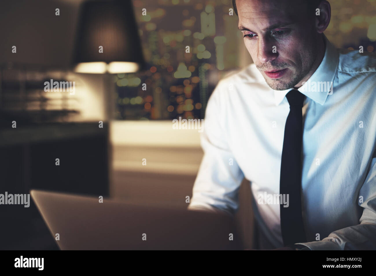 Serious businessman working on laptop at night sitting in office looking concentrated - Stock Image