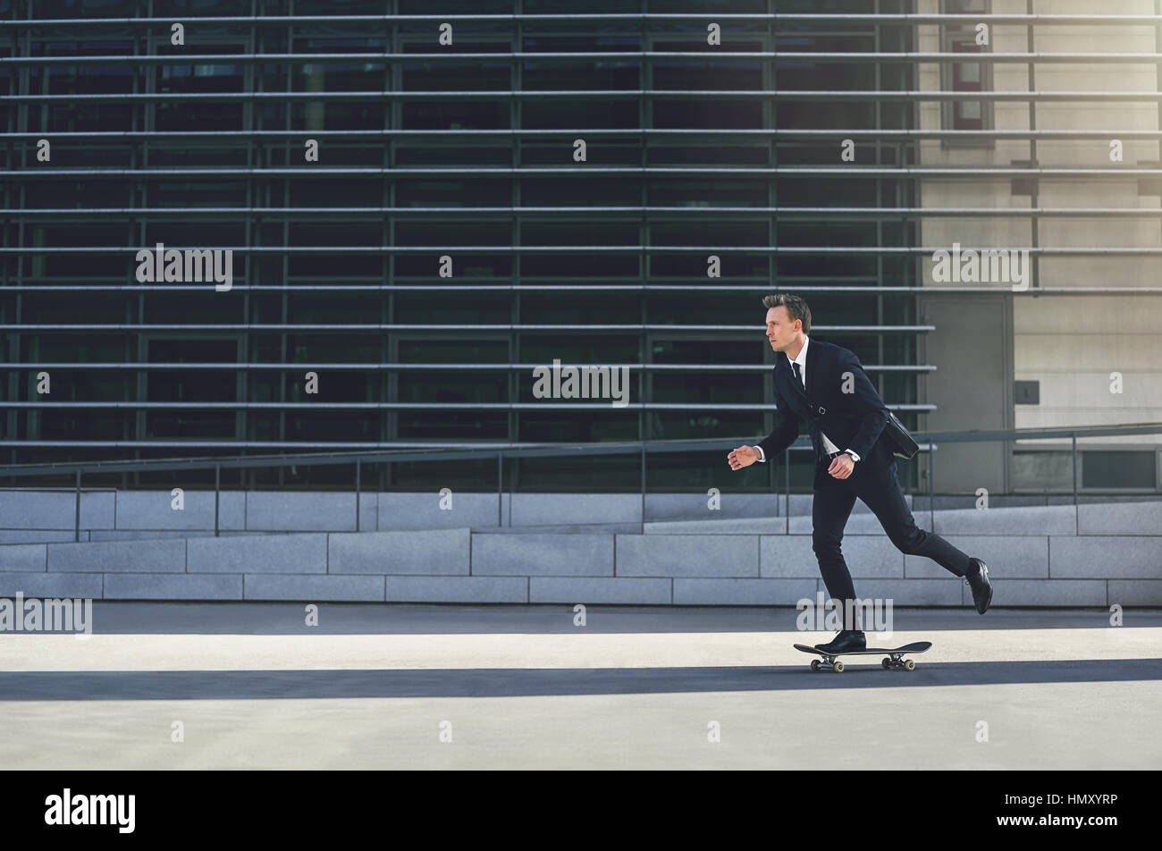 Side view of a businessman pushing himself on a skateboard - Stock Image