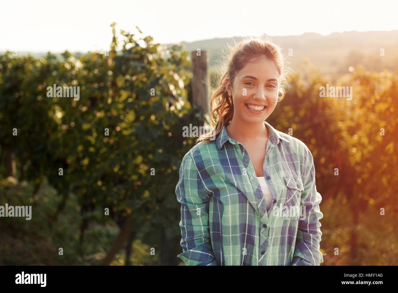 Happy woman in vineyard checking grapes before harvesting - Stock Image