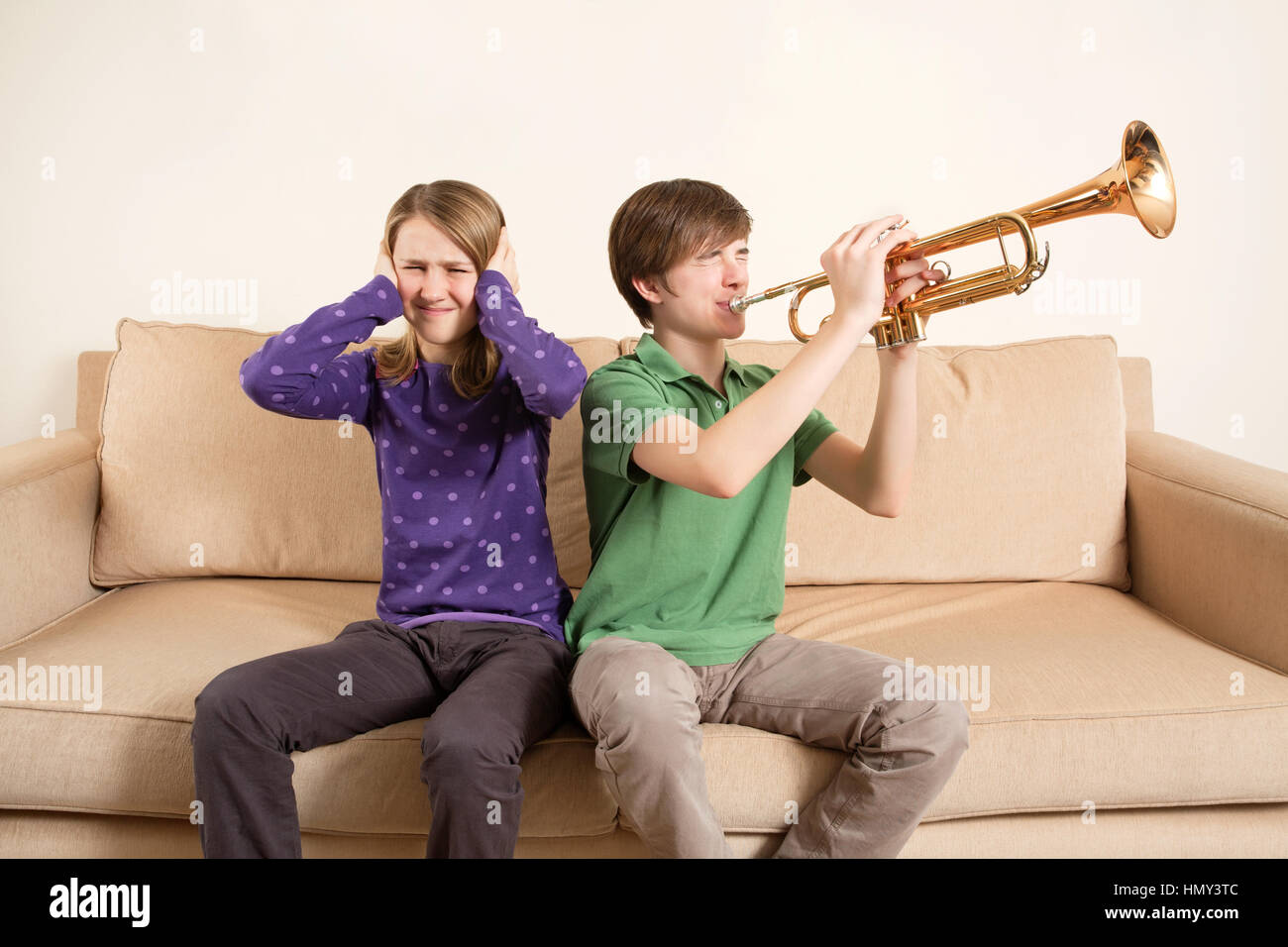 Photo of a brother playing his trumpet too loudly, or badly, and annoying his sister. - Stock Image